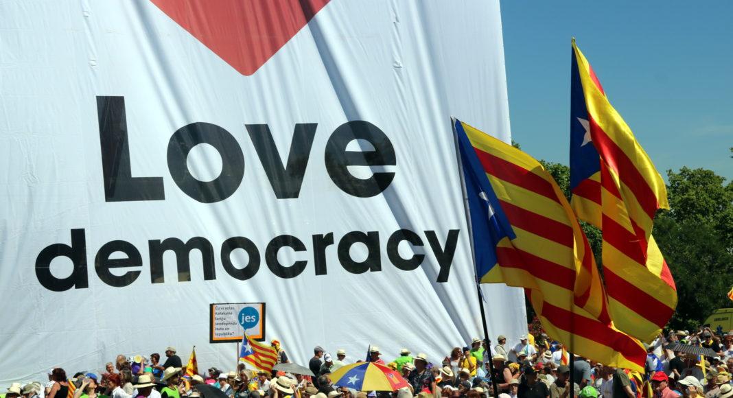 Imatge d'un plafó que ha presidit l'acte en favor del referèndum on es llegeix en anglès 'Estimem la democràcia' / Àlex Recolons