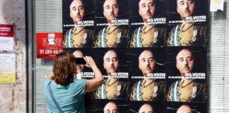 Una dona fa una fotografia a una paret farcida de cartells amb la cara de Franco, al barri de Llefià de Badalona / Jordi Pujolar
