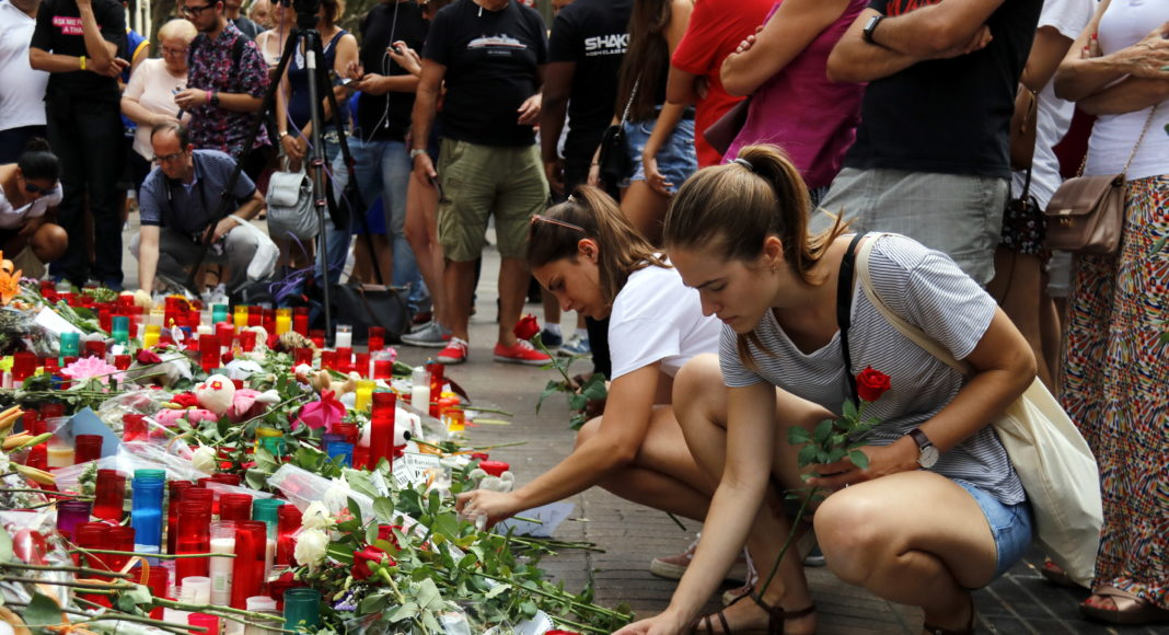 Dues noies encenen espelmes a les Rambles, en un dels punts improvisats de record a les víctimes dels atemptats / Jordi Pujolar