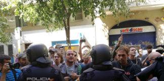 La policia espanyola envoltant la seu de la CUP, mentre simpatitzants criden en contra de l'actuació i en favor de l'1-O / CUP