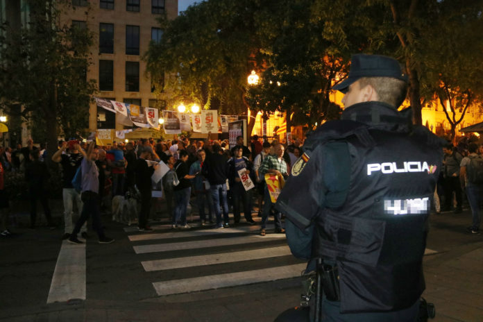 Un agent de la Policia Nacional, d'esquenes, davant de diverses persones convocades per enganxar cartells / Sílvia Jardí