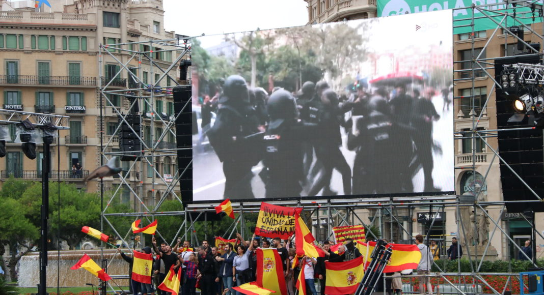 Pla general d'un grup de manifestants espanyolistes cridant, amb banderes espanyoles, sota una pantalla gegant amb imatges de les càrregues policials / Andrea Zamorano