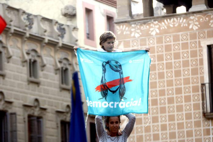 L'enxaneta d'un pilar que han fet els Moixiganguers d'Igualada sosté un domàs de 'Democràcia' / Mar Martí
