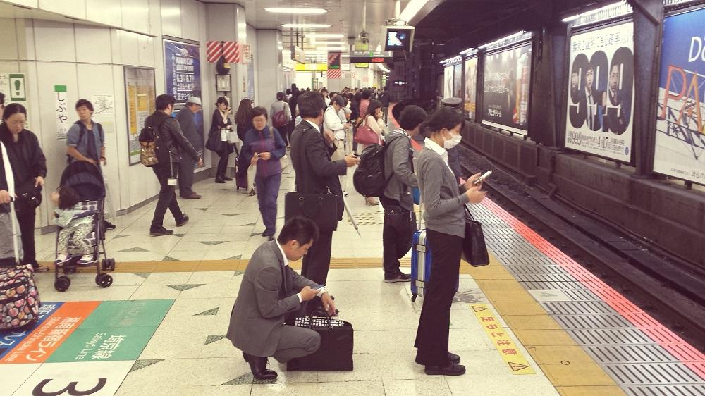 Japonesos esperen ordenadament al metro fent cua davant de la porta corresponent